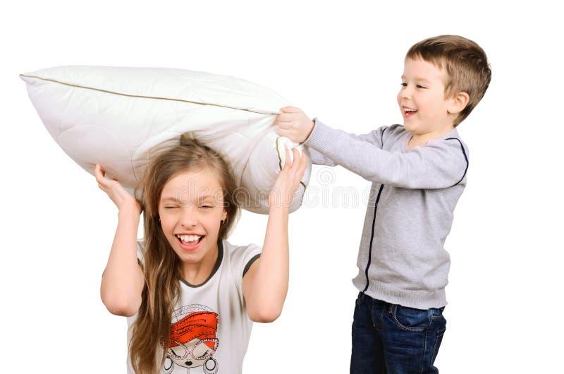 Kämpfendes Kissen des Jungen und des Mädchens stockfotos