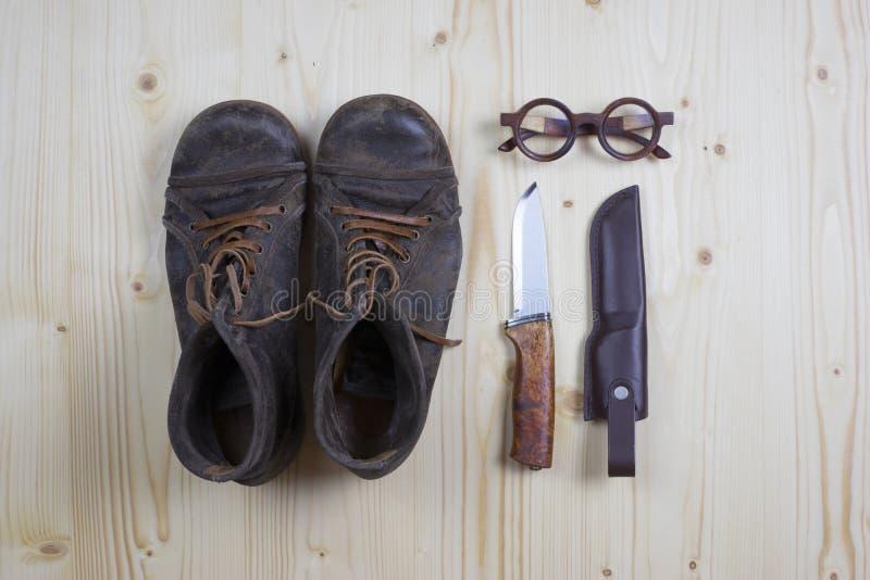 Kängor och kniven sörjer på trä royaltyfri foto