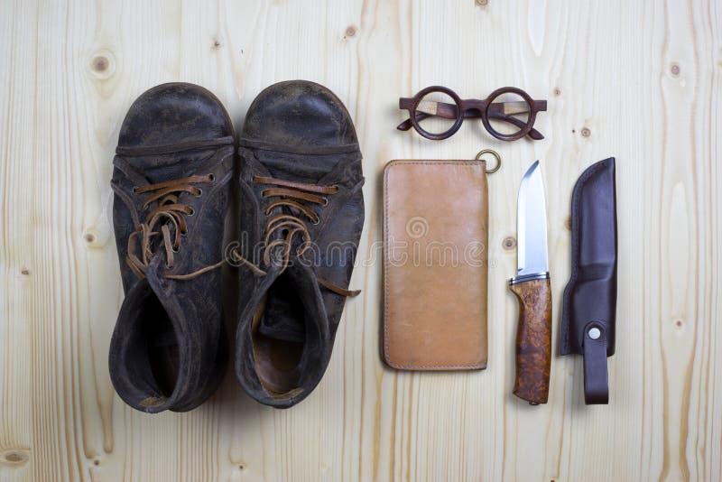 Kängor och läderplånboken på lägenhet sörjer trä royaltyfria foton