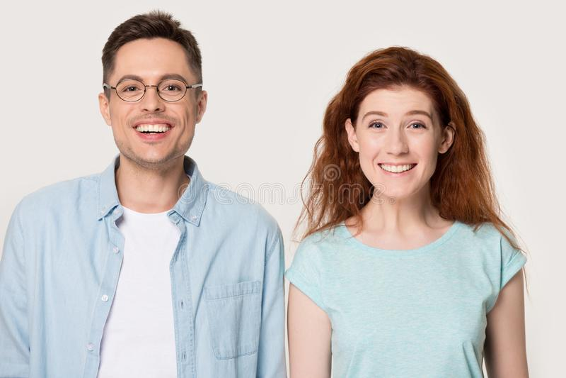 Känner sig det millennial paret för Headshotstudioståenden som ser kameran, lyckligt royaltyfri bild