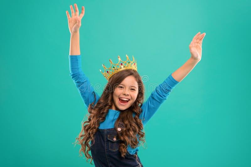 Känner sig som drottning Ungen bär guld- kronasymbol av prinsessan Liten prinsessa för dam Den gulliga flickan behandla som ett b royaltyfria foton
