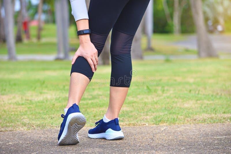 Känseln för ung kvinna smärtar på hennes ben, medan öva arkivbild