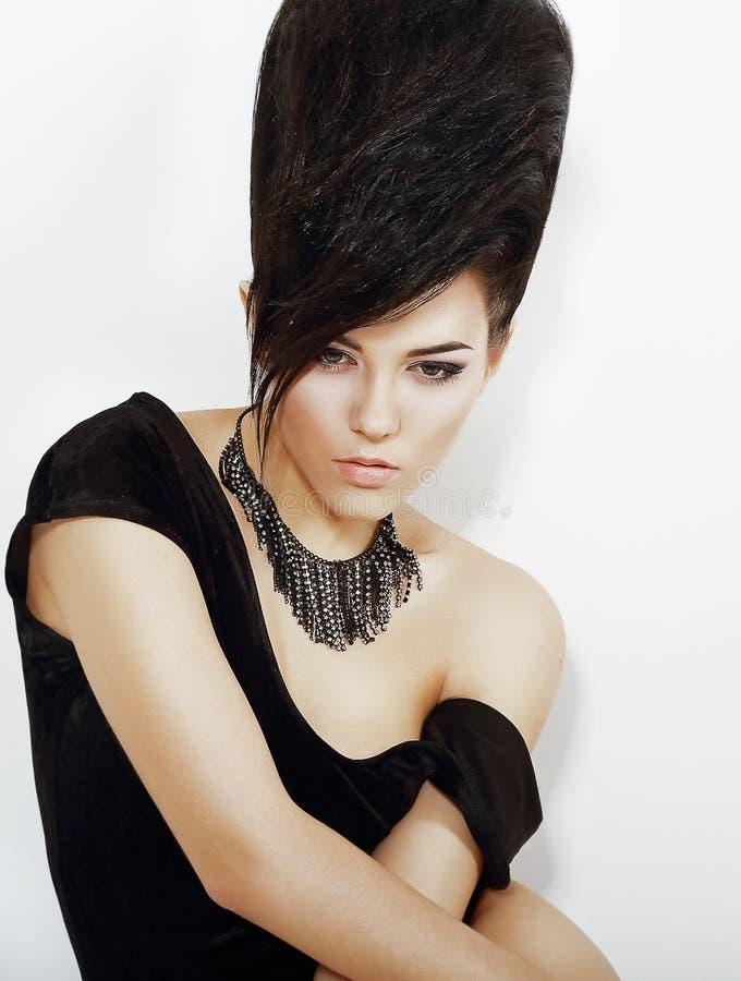 Känsla. Eftertänksam ljus kvinna med svart den Updo hår och halsbandet arkivbild