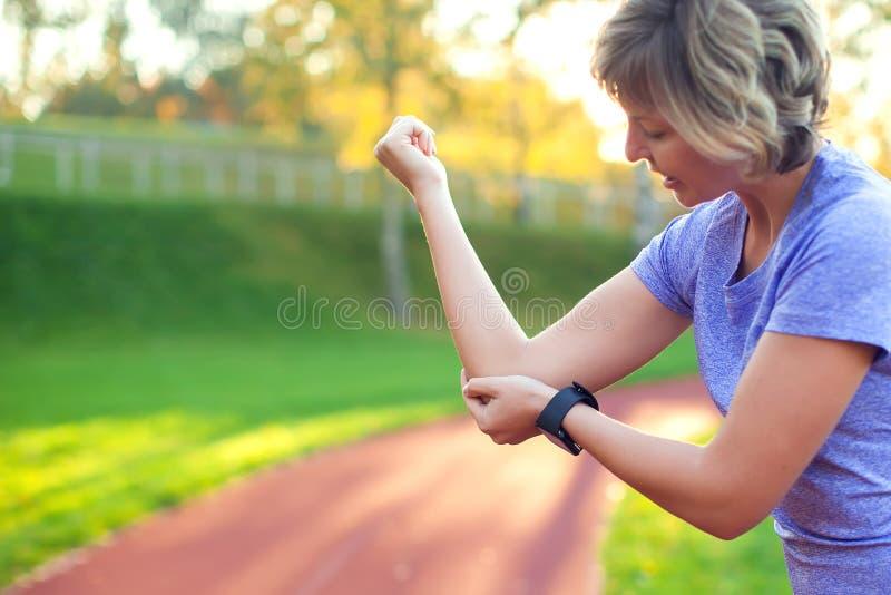 Känsla för den unga kvinnan smärtar i hennes armbåge under sportgenomkörare på st arkivbilder