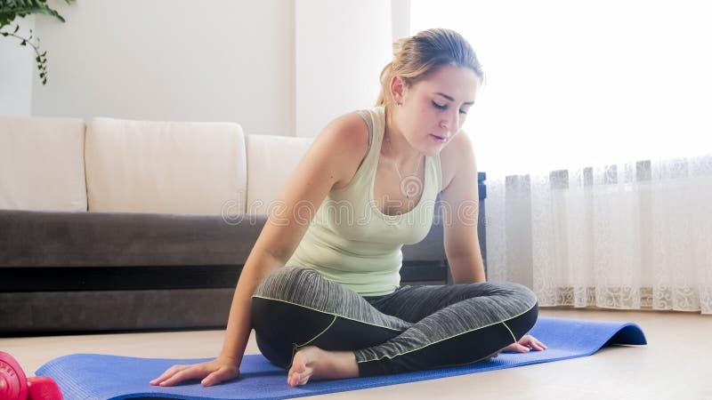 Känsla för den unga kvinnan tröttade, når den har övat på kondition som var matt på vardagsrum fotografering för bildbyråer