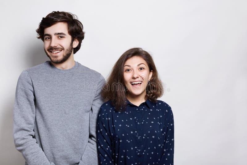 Känsla- och sinnesrörelsebegrepp Ett lyckligt par som nästan står över vit bakgrund som har roliga uttryck arkivbild