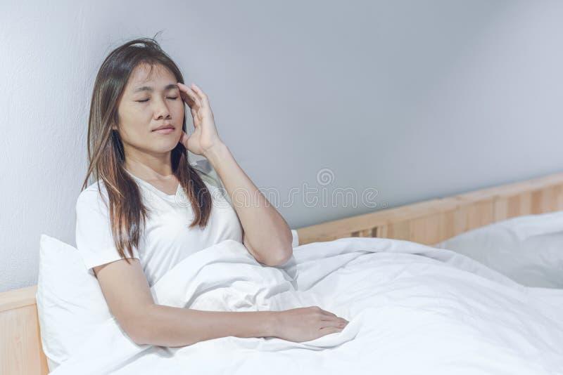 K?nslahuvudv?rk och obehag f?r ung kvinna p? vit s?ng i hennes sovrum fotografering för bildbyråer