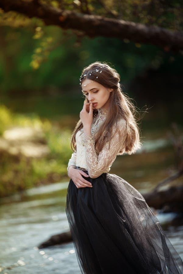 Känslig konststående av den härliga ensamma flickan i den nätta kvinnan för skog som utomhus poserar och ser dig arkivfoto