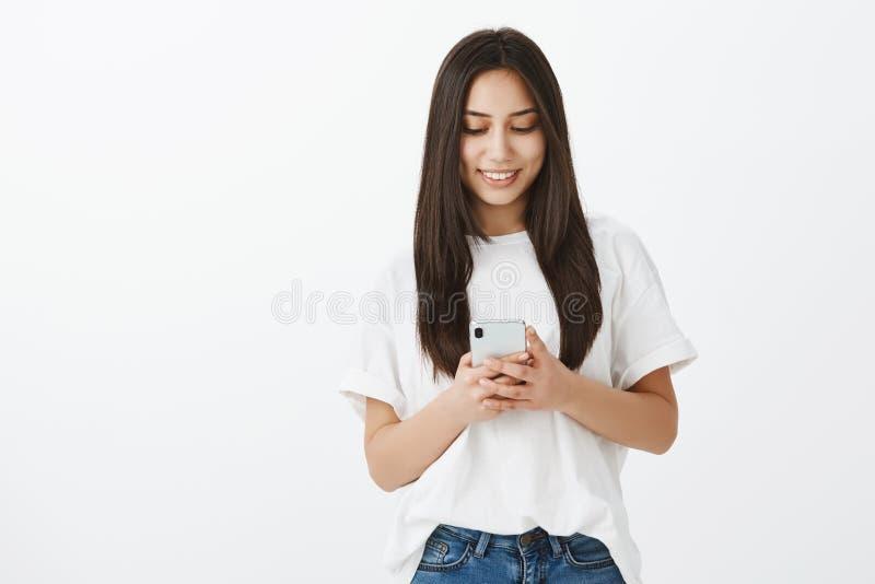 Känslobetonad glad flickvän med brunbränd hud och mörkt hår, hållande smartphone och le på skärmen, medan bläddra in royaltyfri bild