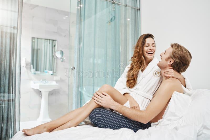 Känslobetonade lyckliga europeiska par som skrattar och kelar, medan sitta i hotellsovrum i dag, bärande pyjamas och arkivfoto