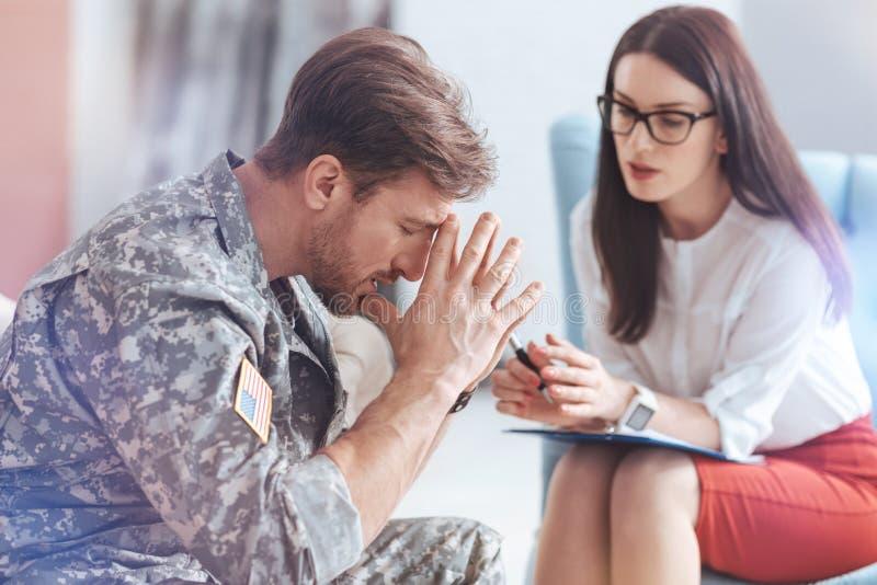 Känslomässigt förstörd militär man som försöker att få på med liv arkivfoto