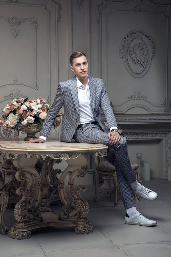 Kär ung man med en frisyr i en dräkt som sitter på en tabell i ett rum med en klassisk inre lyx Manlig skönhet royaltyfria foton