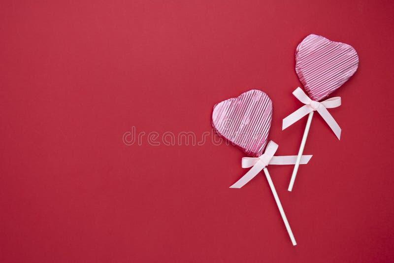 Kärlek, Valentine's Day mock up, flat lay, rosa lollipop i form av ett hjärta isolerat på röd bakgrund, kopieringsutrymme royaltyfria foton