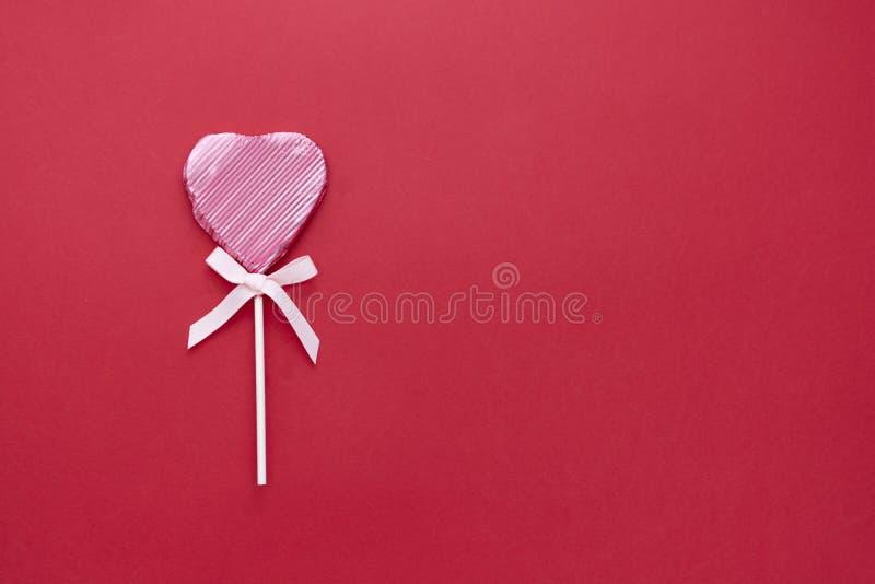 Kärlek, Valentine's Day mock up, flat lay, rosa lollipop i form av ett hjärta isolerat på röd bakgrund, kopieringsutrymme arkivbilder