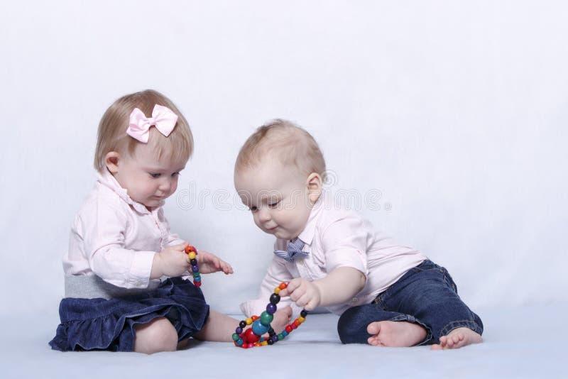 Kärlekshistoria av två gulliga ungar Spädbarnet behandla som ett barn flickan och pojken som spelar med färgrika pärlor royaltyfria bilder