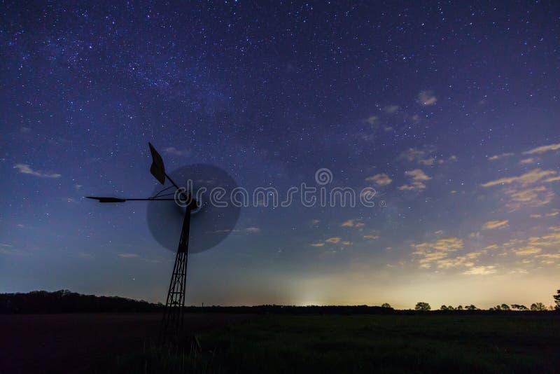 Kärnan för den mjölkaktiga vägen stiger ovanför en väderkvarn i central Tyskland arkivfoto