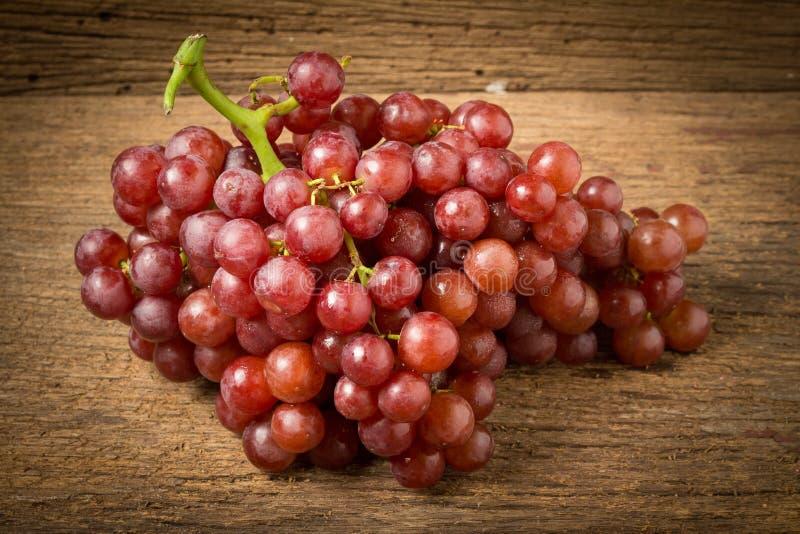 kärnfritt rött för druvor på gammalt trä royaltyfri bild