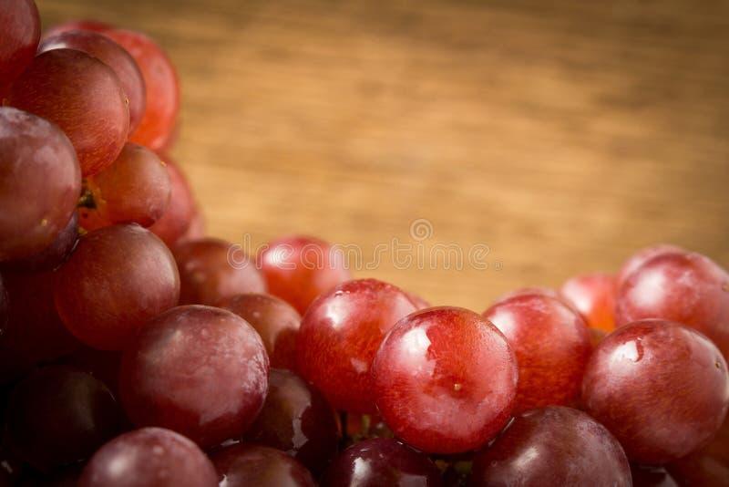 kärnfritt rött för druvor på gammalt trä arkivfoto