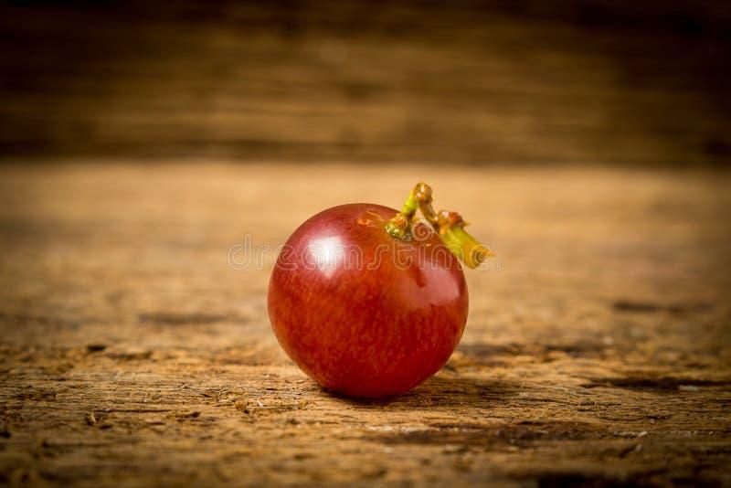 kärnfritt rött för druvor på gammalt trä royaltyfri foto