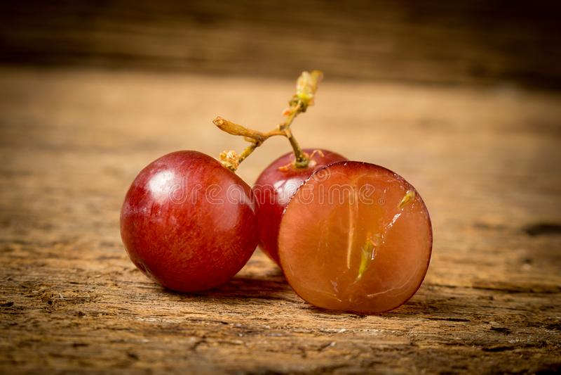 kärnfritt rött för druvor på gammalt trä arkivbild