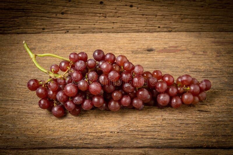 kärnfritt rött för druvor på gammalt trä royaltyfria bilder