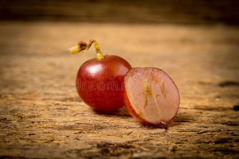 kärnfritt rött för druvor på gammalt trä arkivbilder