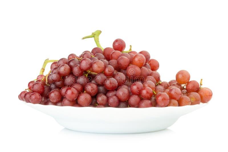 kärnfritt rött för druvor på maträtten som isoleras på vit bakgrund royaltyfri foto