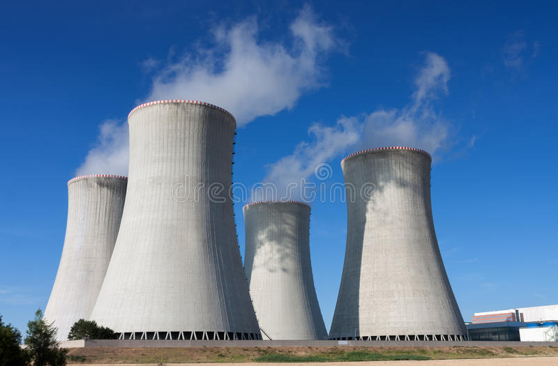 Kärnkraftverket som kyler står högt mot blå himmel royaltyfria foton