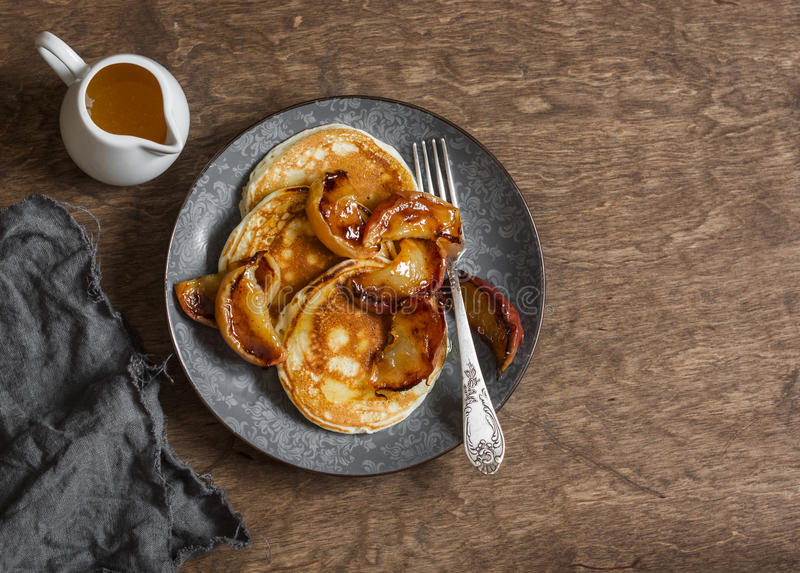 Kärnmjölkpannkaka med grillade honungkaneläpplen Läcker frukost på en trätabell royaltyfria bilder