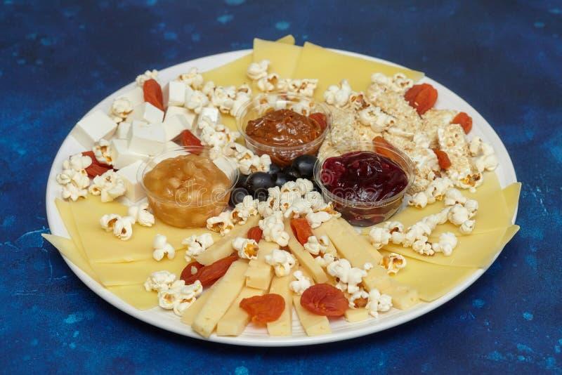 Käse assorti mit Soßen und Popcorn lizenzfreie stockbilder