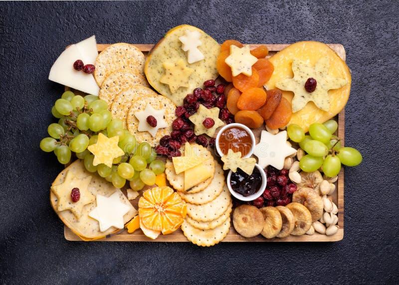 Käse auf Holzbrettplatten Hartkäse Scheiben, Walnüsse, Trauben, Cracker, Chutney Mango, Konfitüre, dunkler Hintergrund, oben stockbild