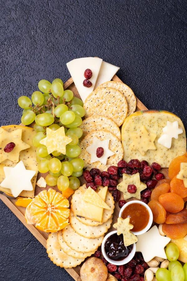 Käse auf Holzbrettplatten Hartkäse Scheiben, Walnüsse, Trauben, Cracker, Chutney Mango, Konfitüre, dunkler Hintergrund, oben stockfotografie