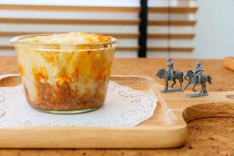 Käse backte Penne in der Glasschüssel auf hölzerner Platte mit grauen Farbcowboy-Reitminiaturpferden stockfotos