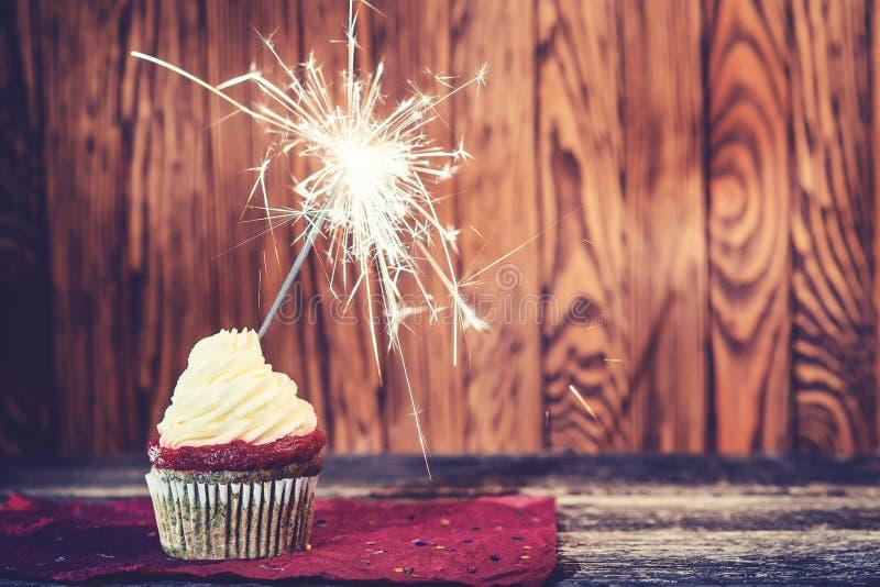 Käse des kleinen Kuchens mit Sahne, mit Wunderkerze auf dunklem hölzernem Hintergrund lizenzfreie stockfotografie