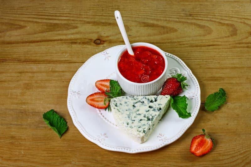Käse dourble oder Briekäse mit blauer Form mit Erdbeermarmelade und Minze auf einer weißen Platte, hölzerner Hintergrund Lebensmi stockbild