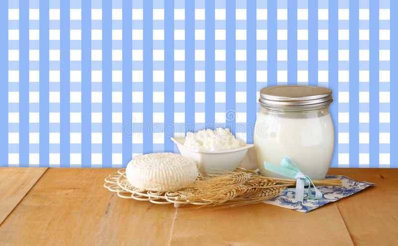 Käse, Häuschen und Milch Tzfatit auf Holztisch über Retro- ländlichem Hintergrund jüdisches Feiertag Shavuot-Konzept lizenzfreies stockbild