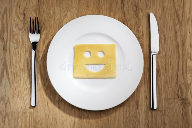 Käse mit lächelndem Gesicht auf einer Tabelle stockfotografie