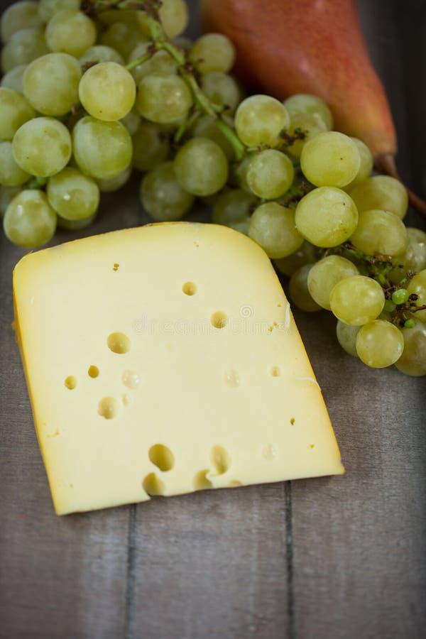 Käse mit Trauben und Birne auf hölzernem Behälter lizenzfreie stockfotos