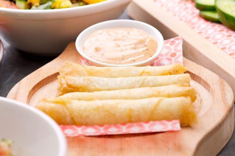 Käse rollt Platte mit der Cocktailsauce, die in einer hölzernen Platte auf einem rustikalen Ba gedient wird lizenzfreies stockfoto