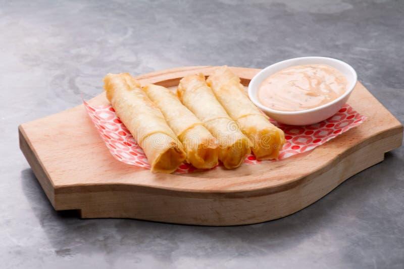 Käse rollt Platte mit der Cocktailsauce, die in einer hölzernen Platte auf einem rustikalen Ba gedient wird stockfoto