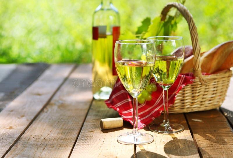 Käse, Trauben, Brot und zwei Gläser des Weißweins stockbild