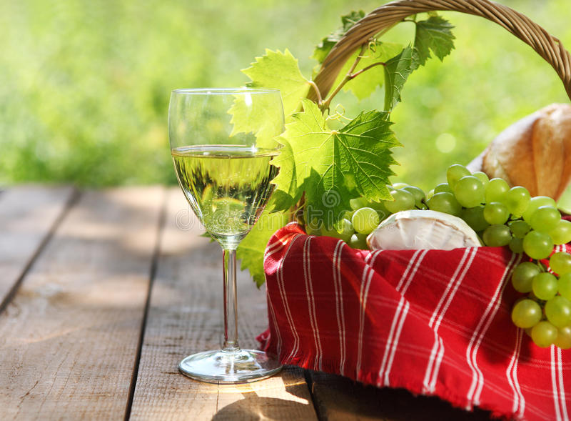 Käse, Trauben, Brot und zwei Gläser des Weißweins stockbilder