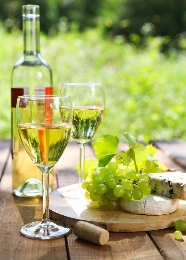 Käse, Trauben und zwei Gläser des Weißweins stockfoto