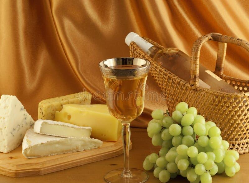 Käse und Trauben mit Glas weißem Wein lizenzfreies stockbild