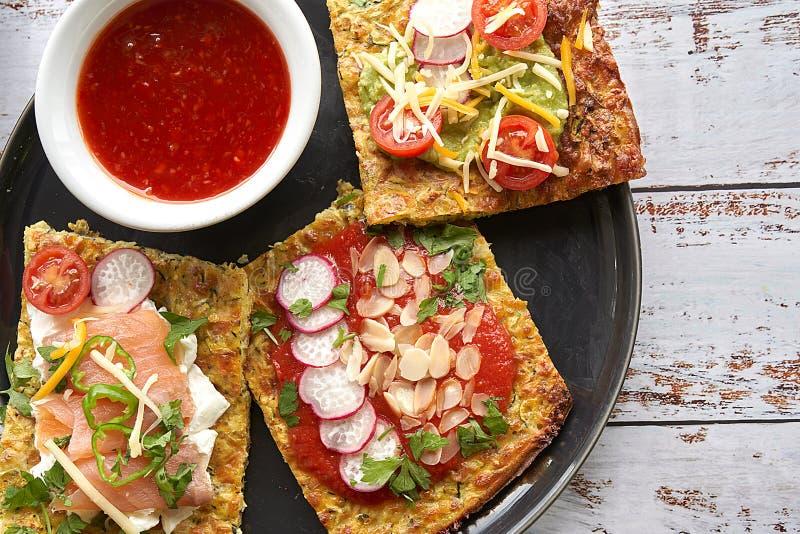 Käse- und Zucchinitortillas, geräucherter Lachs, raishes, Kirschtomaten, Avocadocreme, Frischkäse, Tomatencreme mit Basilikum lizenzfreie stockbilder