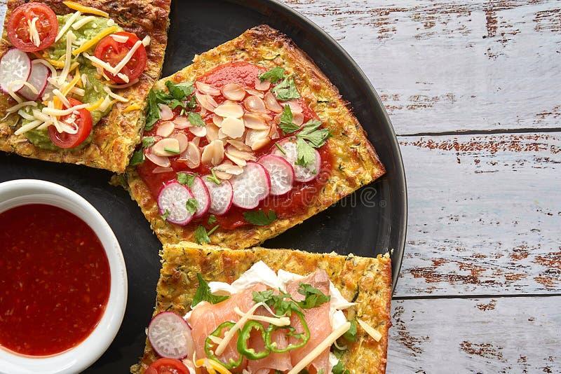Käse- und Zucchinitortillas, geräucherter Lachs, raishes, Kirschtomaten, Avocadocreme, Frischkäse, Tomatencreme mit Basilikum lizenzfreies stockbild
