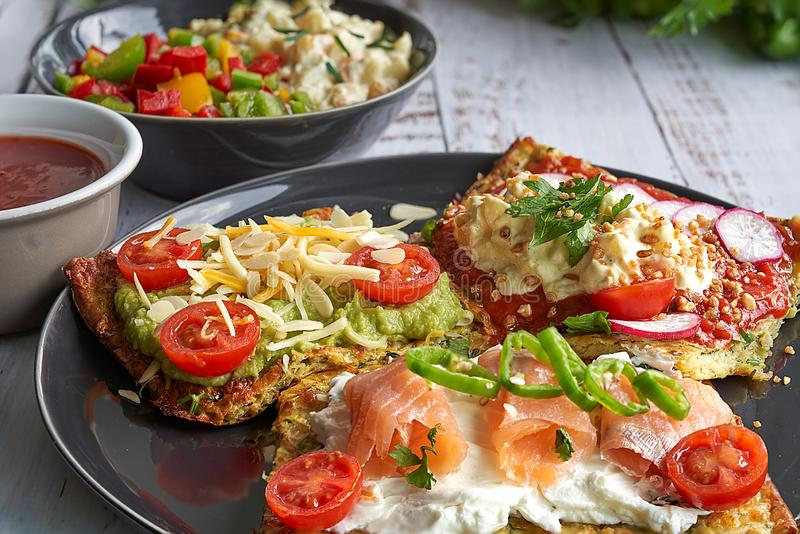 Käse- und Zucchinitortillas, geräucherter Lachs, raishes, Kirschtomaten, Avocadocreme, Frischkäse, Tomatencreme mit Basilikum, stockfotografie