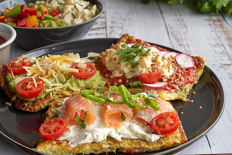 Käse- und Zucchinitortillas, geräucherter Lachs, Rettiche, Kirschtomaten, Avocadocreme, Frischkäse, Tomatencreme mit Basilikum, G stockfoto