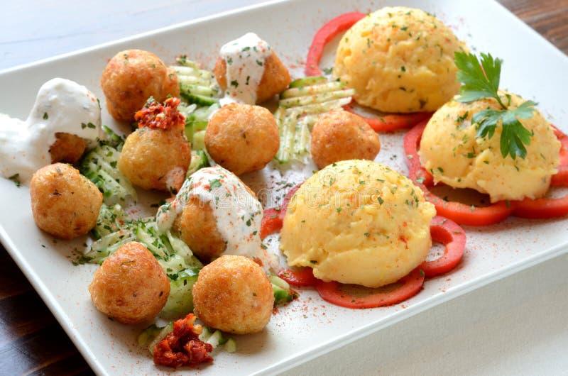 Käsebälle mit Kartoffelpuree auf einer weißen Platte stockfoto