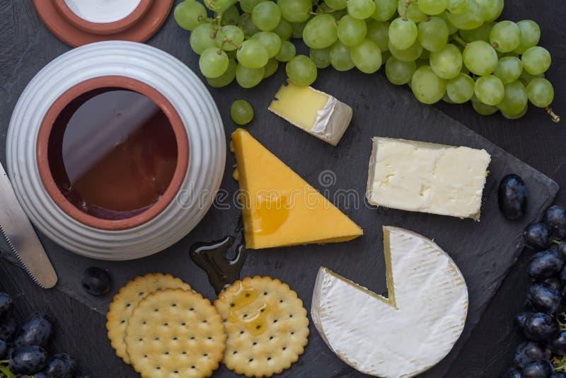 Käsebrett mit Cheddarkäse, Camembert, Trauben, Cracker und Honig schließt herauf - obenliegendes Foto lizenzfreie stockfotos